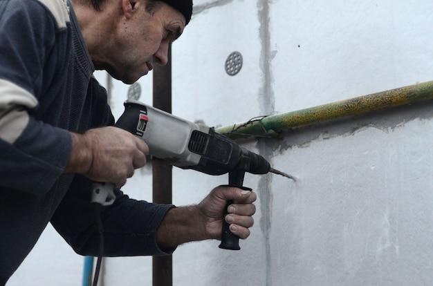 An elderly workman drills a hole in a styrofoam wall Premium Photo