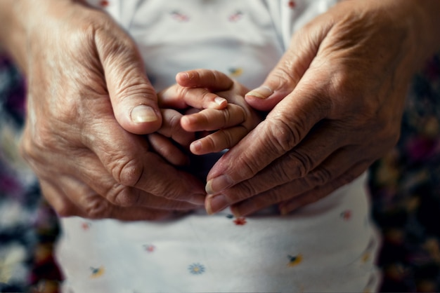 Eldery hands holding newborn young hands; grandparent Premium Photo