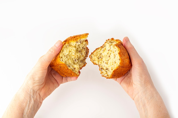 Eldery woman's hands hold (break) small freshly baked homemade whole-grain bread on white background. helping hand concept, close up Premium Photo