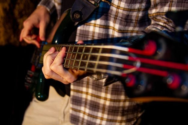 Electric bass guitar player, closeup photo with soft selective focus Premium Photo