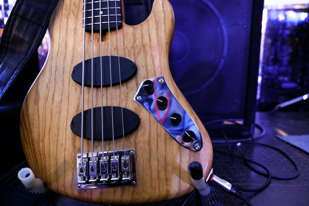 Electric bass guitar stands on the stage. close up. Premium Photo