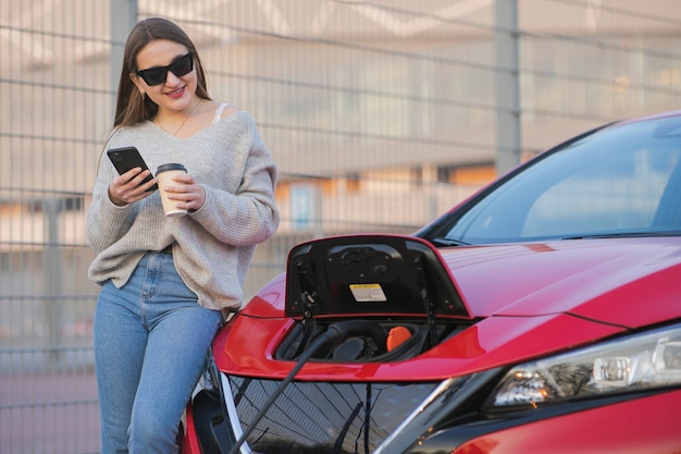 Electric car charging in street. ecological car connected and charging batteries. girl use coffee drink while using smartphone and waiting power supply connect to electric vehicles for charging Premium Photo