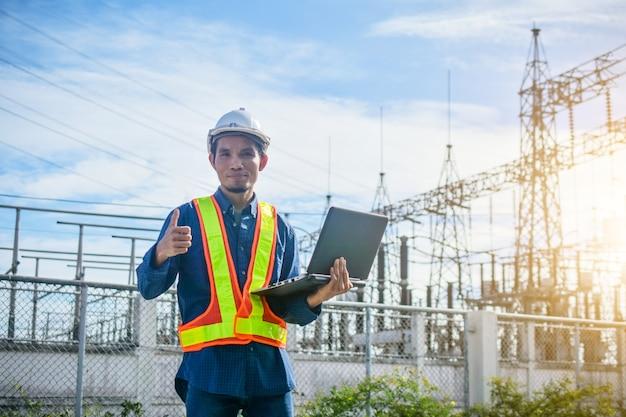 電気技師保持コンピューターノートブック工場発電所システムの背景 Premium写真