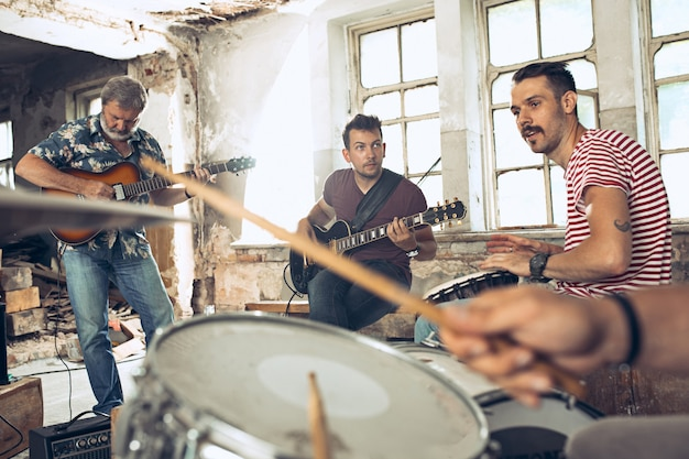Electric guitar players and drummer behind the drum set. Free Photo
