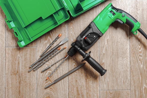 Electric hammer drill lies on a wooden table Premium Photo