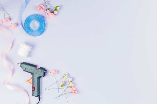 Electric hot glue gun; thread spool; ribbon and artificial roses isolated on white backdrop Free Photo