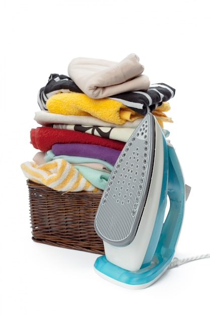 Electric iron and pile of clothes. Premium Photo