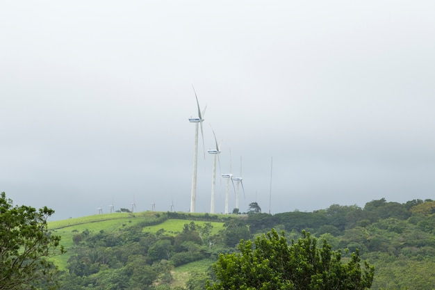 Electric power production of windmill on mountain top Free Photo