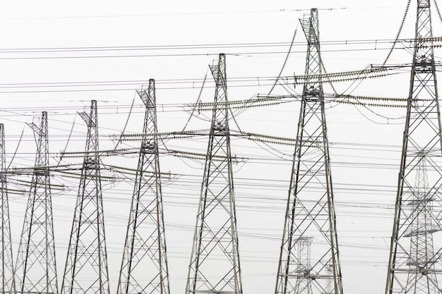 Электроэнергия передает высоковольтную башню на фоне неба тумана. Premium Фотографии