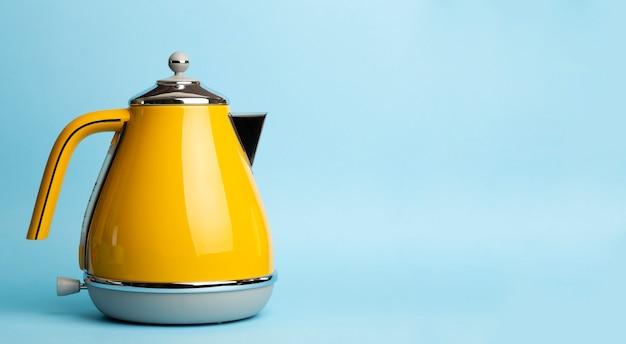 色付きの青い背景に電気ヴィンテージレトロなやかん。ライフスタイルとデザインコンセプト Premium写真