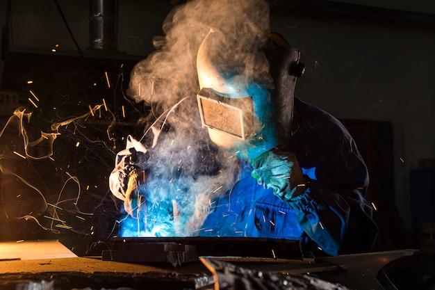 Электросварщик работает с аргоновой сваркой, сварщик в маске во время работы над деталями Premium Фотографии