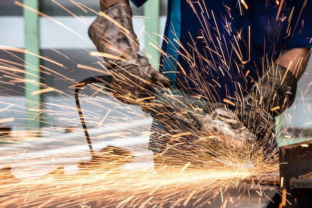 Electric wheel grinding on steel structure in factory Premium Photo