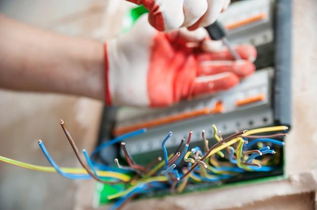 Электрические провода торчат из распределительной коробки. Premium Фотографии
