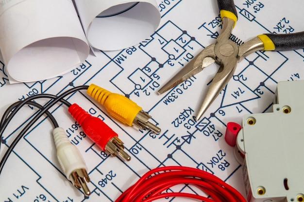 電気回路図、アクセサリー、エンジニアリングプロジェクトの家のコンセプトを構築する金属ペンチ Premium写真