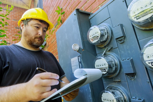 Инженер-электрик во время проверки в желтом шлеме, техник изучает показания счетчика в буфере обмена Premium Фотографии