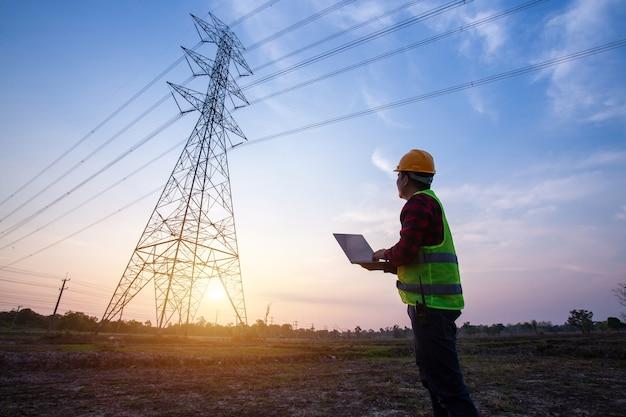 Инженер-электрик стоит и смотрит на электростанции Premium Фотографии