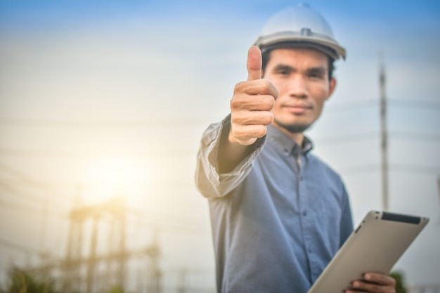 Electrical engineer uses a tablet to inspect power plant network for power generation Premium Photo