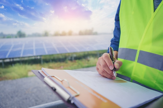Electrical and instrument technician make a note statistic chart electric system at solar panel field. Premium Photo