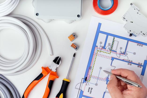 Электрик проверяет электрические планы. концепция ремонта электрооборудования. Premium Фотографии