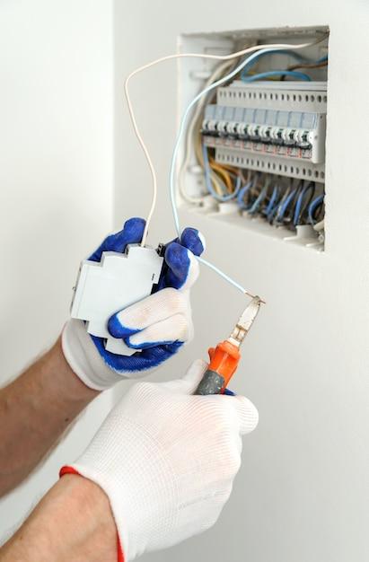 Электрик отрезает провод нужной длины при установке электрооборудования. Premium Фотографии