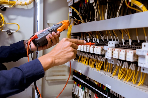 Измерения электрика с мультиметром, проверяющим электрический ток в пульте управления Premium Фотографии