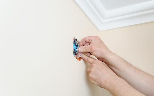 Руки электрика проталкивают провод в распределительной коробке Premium Фотографии