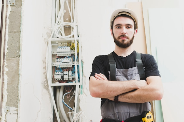 Electrician standing at cables in wall Free Photo