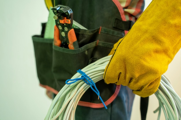 Electrician with special tools,electrician with bunch of wires indoors. Premium Photo