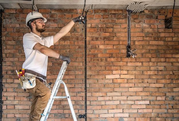 Электрик с инструментами, работает на строительной площадке Бесплатные Фотографии