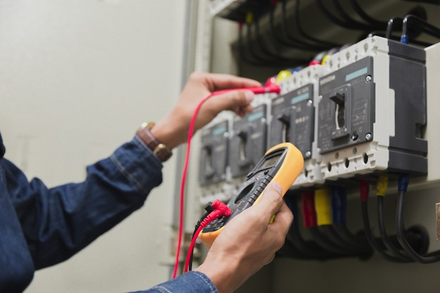 Electrician work  tester measuring  voltage of power electric line. Premium Photo