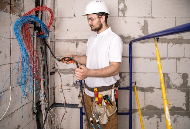 Electrician working near the board with wires. installation and connection of electrics. Free Photo
