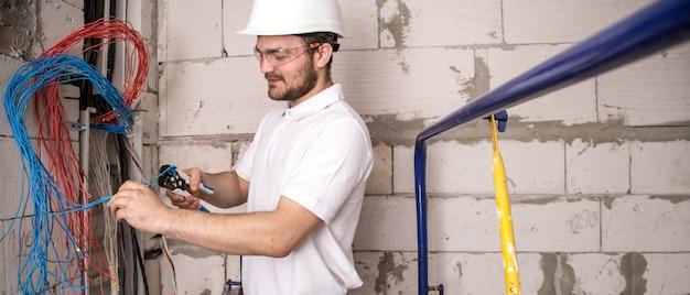 Elettricista che lavora vicino alla scheda con fili. installazione e collegamento dell'impianto elettrico. Foto Gratuite