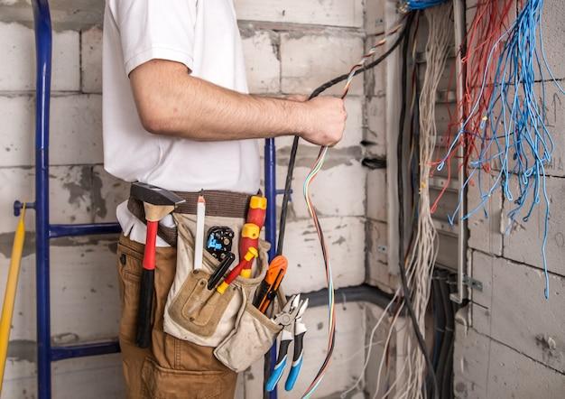 Электрик работает возле доски с проводами. монтаж и подключение электрики. Бесплатные Фотографии