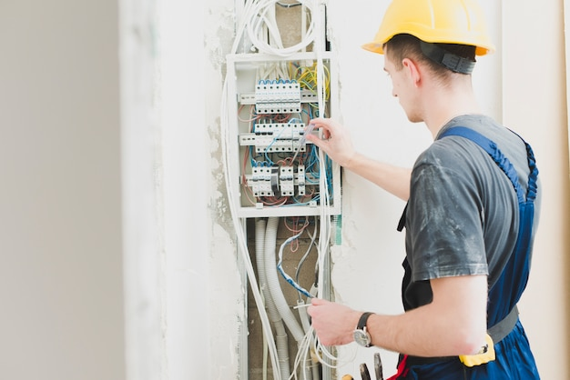 Electrician working with switchboard Free Photo
