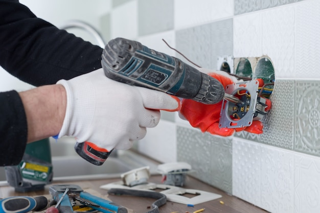 Electricians hand installing outlet on wall with ceramic tiles using professional tools Premium Photo