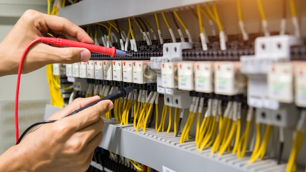 Electricians hands testing current electric in control panel. Premium Photo