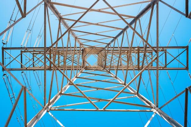 電気は、金属製の塔に取り付けられた太いケーブルによって運ばれます。 Premium写真