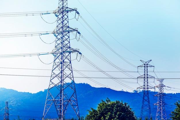 Пилон передачи электроэнергии вырисовываются на фоне голубого неба в д Бесплатные Фотографии