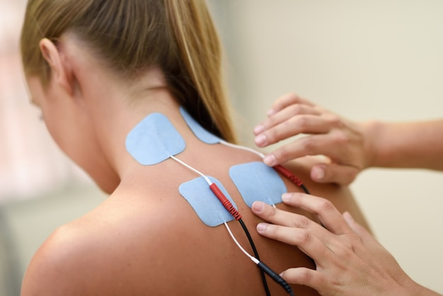 Electro stimulation in physical therapy to a young woman Free Photo