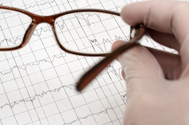 Рука в белой медицинской перчатке держит очки. electroca Premium Фотографии