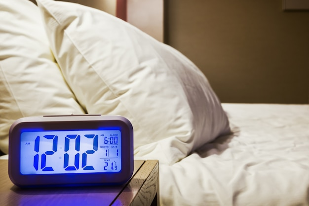 Electronic alarm clock stands on a bedside table in the room Premium Photo