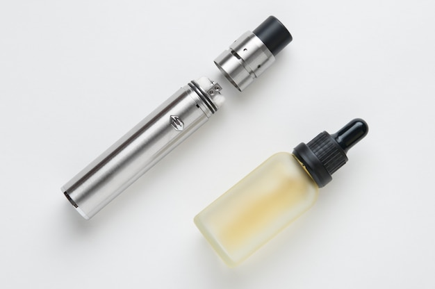 Electronic cigarette and bottle of liquid. Premium Photo