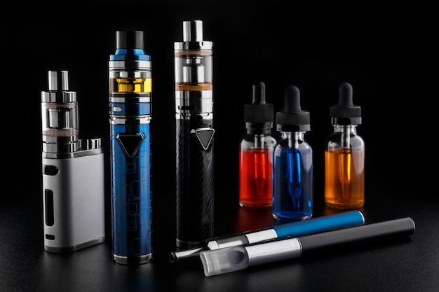 Electronic cigarettes and bottles with vape liquid on black background Premium Photo