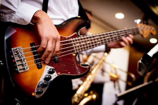 Electronic guitar in the hands of a man dressed in a white shirt Premium Photo