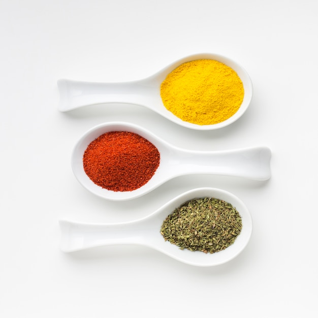 Elegant aligned spoons with spices powder Free Photo