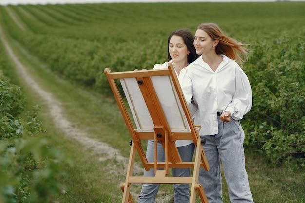 Элегантные и красивые девушки рисуют в поле Бесплатные Фотографии