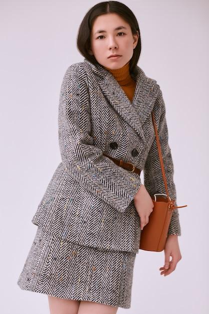 Elegant asian woman in fashionable woolen coat and classic skirt Premium Photo