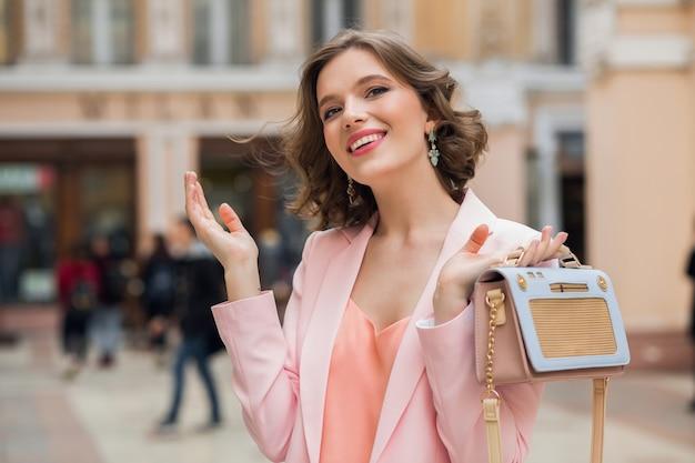 Элегантная привлекательная улыбающаяся женщина с вьющейся прической гуляет по городу Бесплатные Фотографии