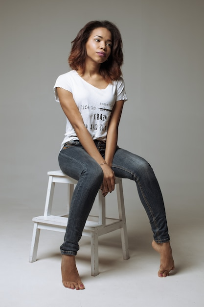 Elegant beautiful african american woman sitting in a contemporary chair Premium Photo