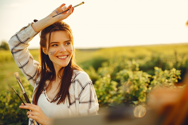 Elegant and beautiful girl painting in a field Free Photo